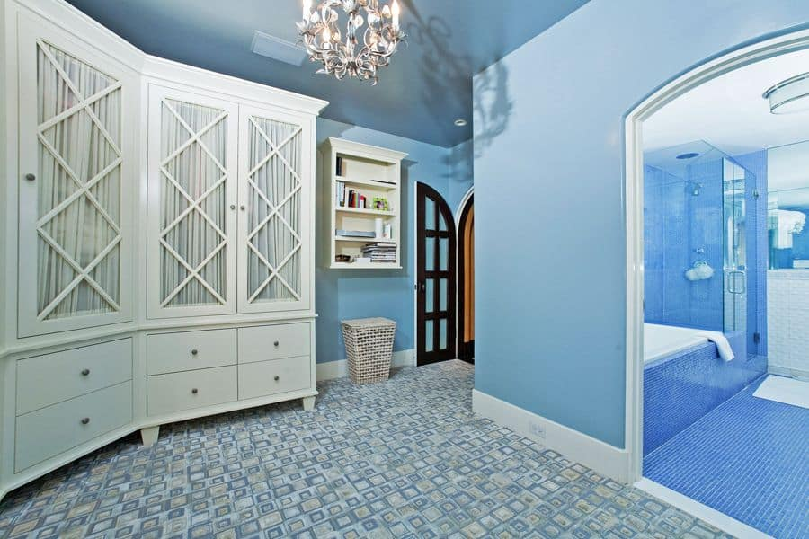 Primary bathroom with a closet area lighted by a gorgeous chandelier. The bathroom has blue tiles floors and walls. It also has a drop-in tub and a walk-in shower room.