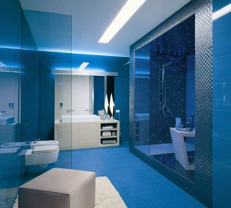 Custom primary bathroom with blue tiles floors and blue walls, along with stunning lighting. The room offers a modern sink counter with a large sink and a stylish walk-in shower room.