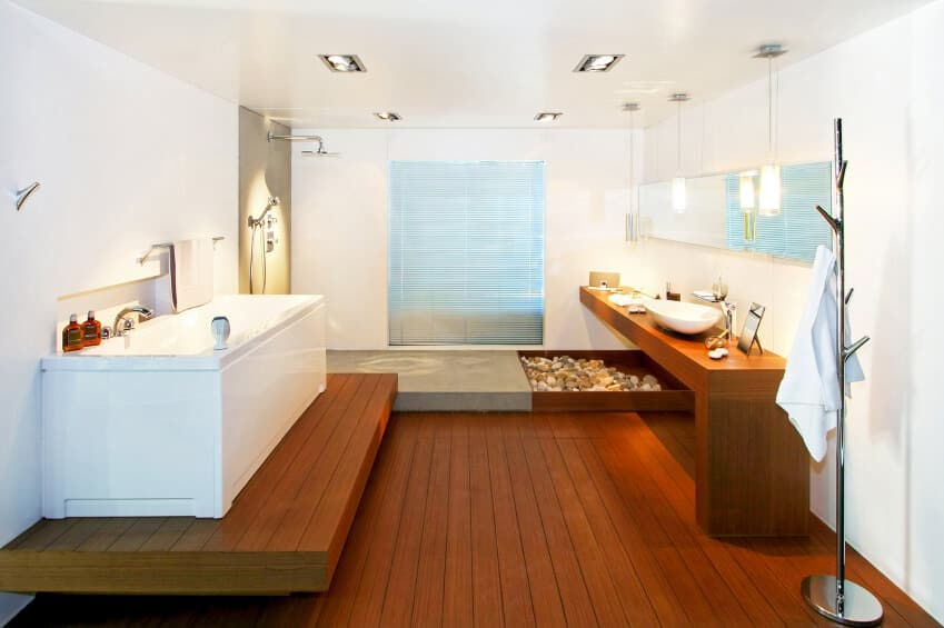 Primary bathroom with stylish hardwood flooring and a hardwood bathtub platform. There's also a stunning sink counter with a vessel sink, along with an open shower.