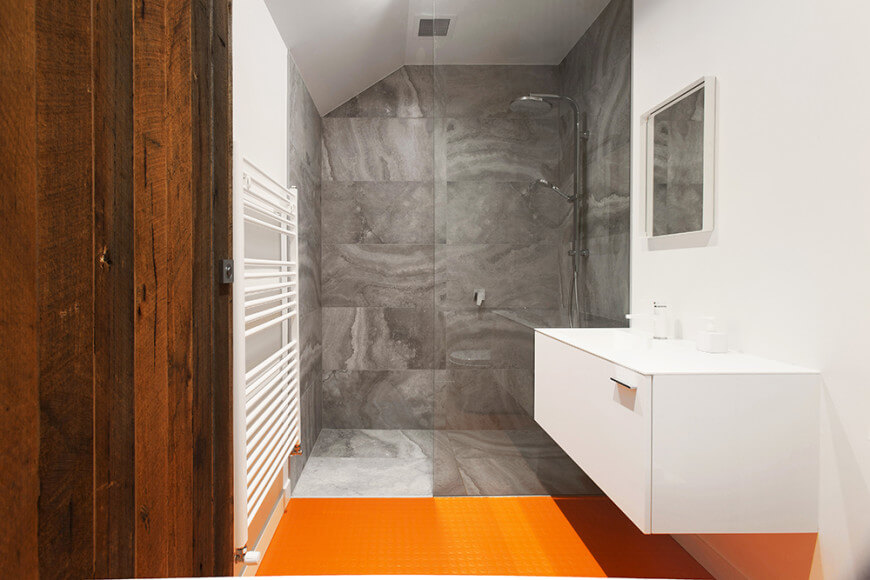 Small custom primary bathroom featuring orange tiles floors and white walls, along with a floating vanity sink. There's a walk-in shower as well featuring gray tiles floors and walls.