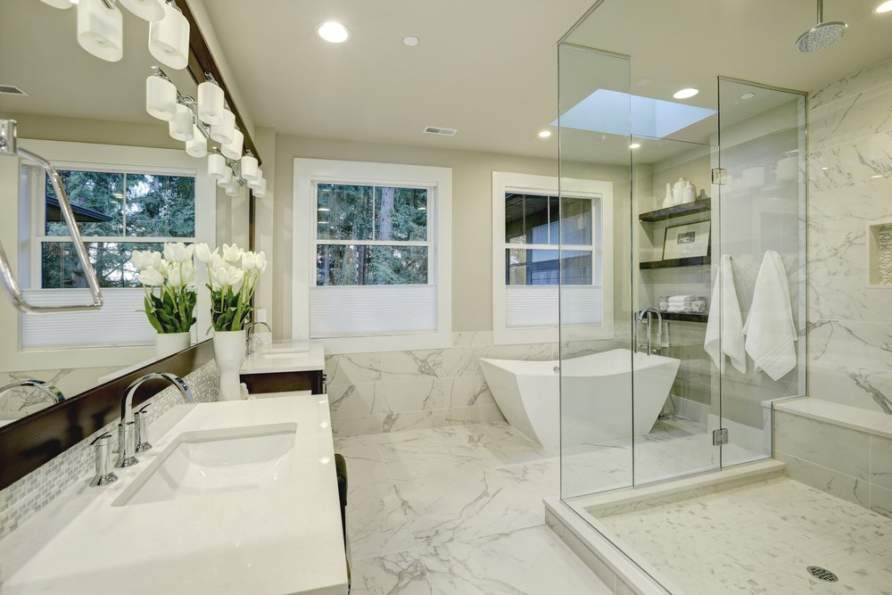 This primary bathroom boasts marble tiles floors along with a pair of sink counters and a freestanding soaking tub set under the skylight. There's a large walk-in shower as well.