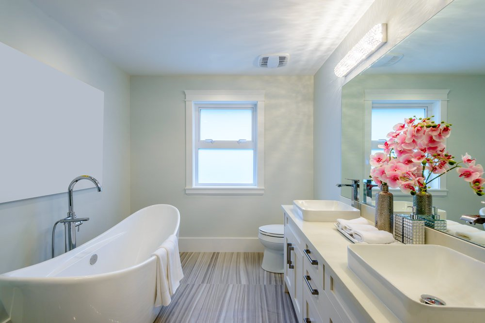 Small primary bathroom featuring stylish flooring and beige walls. The room offers a large freestanding soaking tub and a sink counter with lovely sinks.