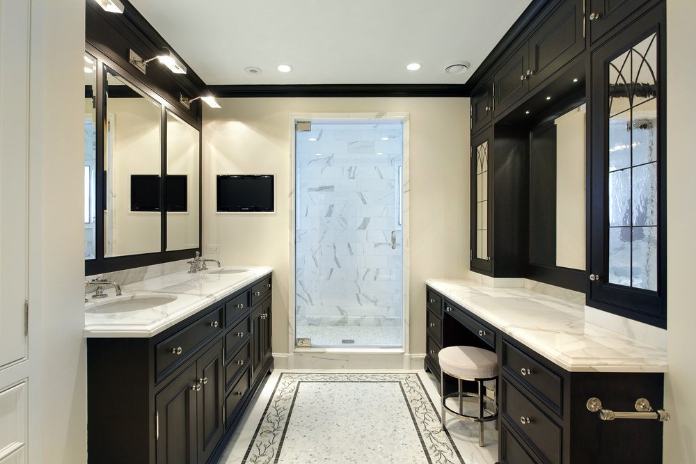 Primary bathroom with a walk-in shower, a sink counter with a double sink and a powder desk, both featuring classy marble countertops.