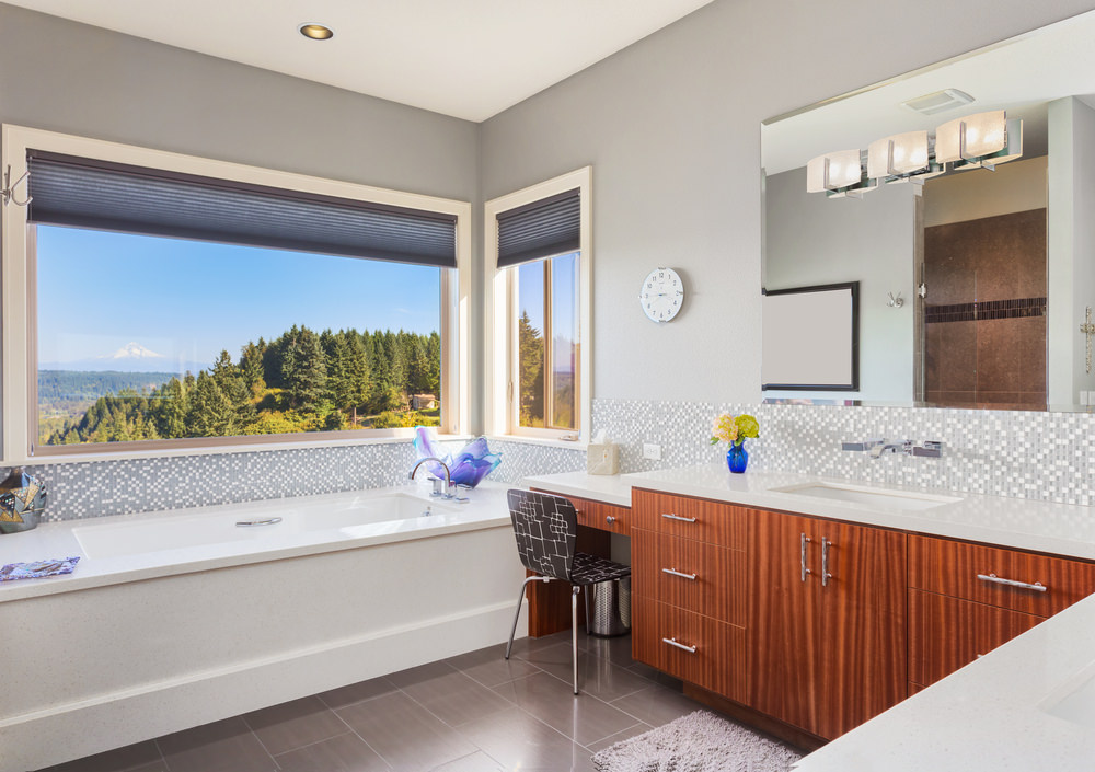 A custom primary bathroom featuring a stylish sink counter with a powder desk on the side. There's a drop-in soaking tub set near the glass windows overlooking the peaceful surroundings.