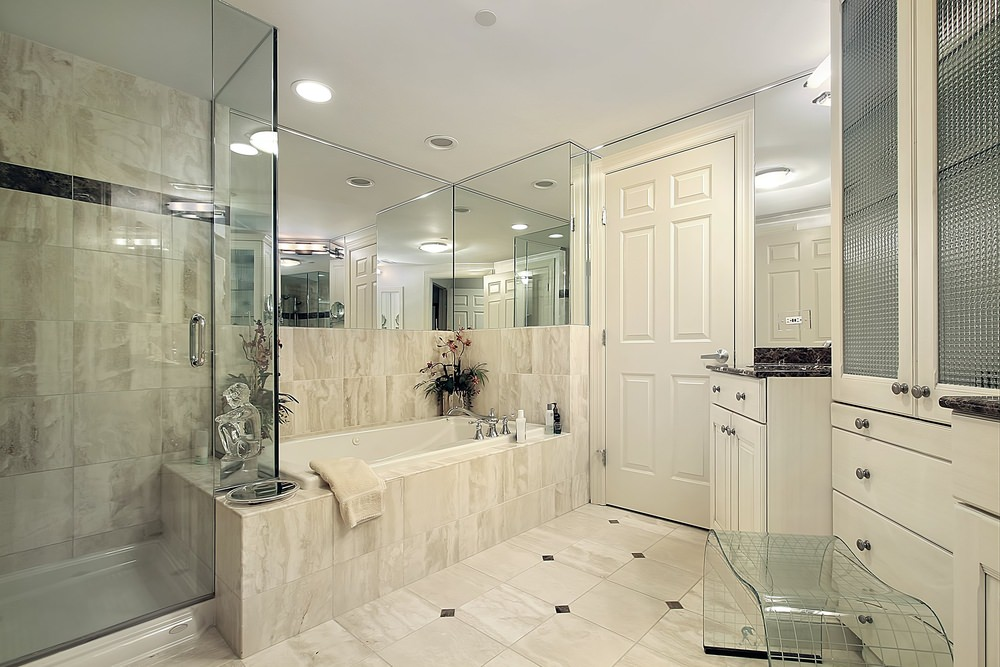 Primary bathroom with classy tiles flooring. It has a single sink counter in the corner, together with the drop-in soaking tub and the walk-in shower room on the side.