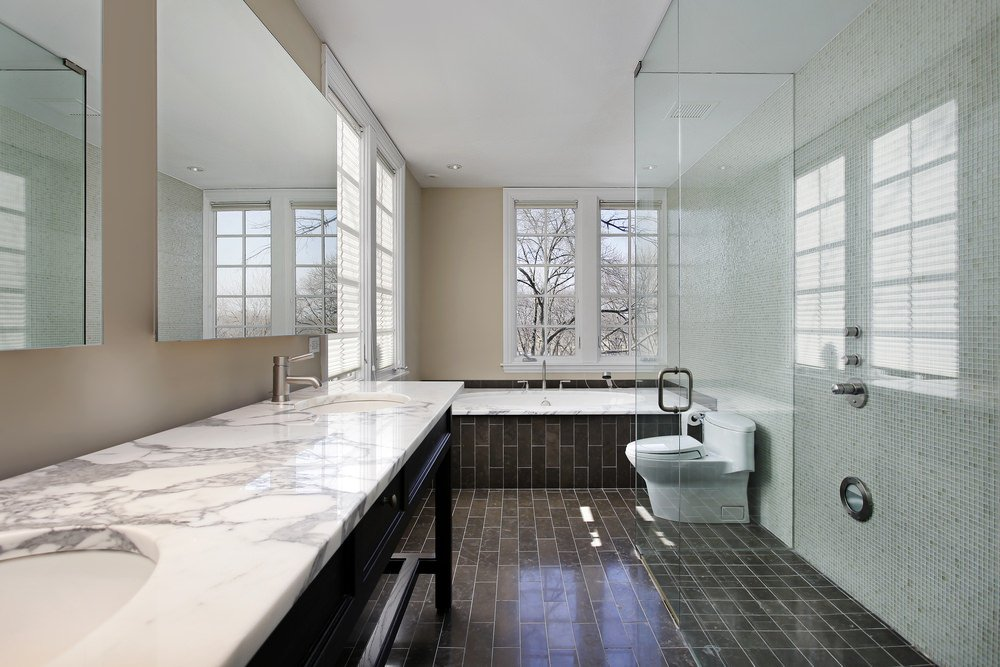 This primary bathroom boasts black tiles flooring and a sink counter with a marble countertop and has two sinks. There's a walk-in glass shower and a drop-in soaking tub as well.