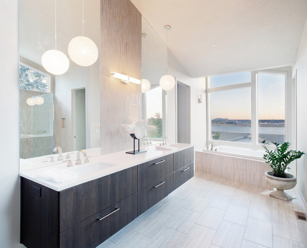 Bright primary bathroom with a shed white ceiling and white walls, along with glass windows overlooking the striking surroundings. The room offers a walk-in shower room and a toilet room, along with a drop-in bathtub and a sink counter with two sinks, lighted by charming pendant lights.