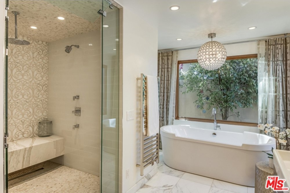 Small primary bathroom featuring marble tiles flooring and a regular ceiling. There's a large freestanding deep soaking tub by the window and a walk-in shower room on the side.