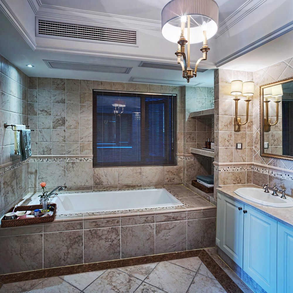 This bathroom boasts a custom bathtub area with a brown tiles platform and built-in shelving. The room also has a tray ceiling where the gorgeous ceiling light is set.
