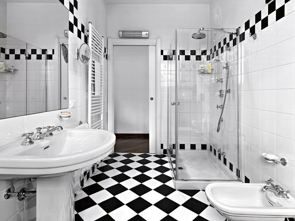 Primary bathroom boasting checker tiles flooring that looks stylish. It has a pedestal sink and a glass walk-in shower.