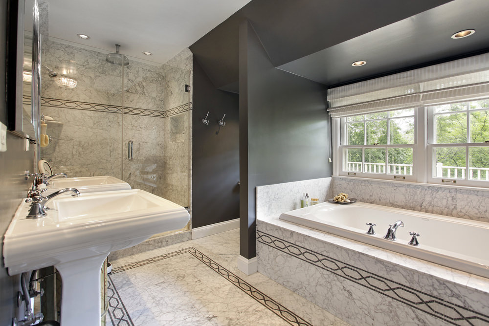 This primary bathroom boasts classy decorated tiles flooring and black walls. It offers a pair of pedestal sinks and a drop-in soaking tub by the windows, along with a walk-in shower area.