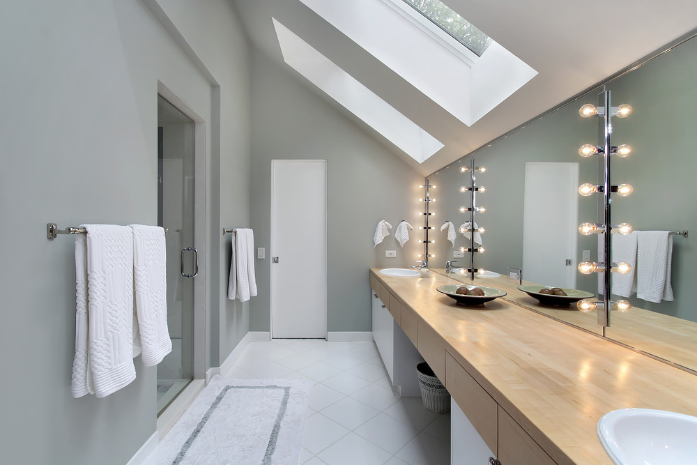Custom primary bathroom featuring white tiles flooring, gray walls and a shed ceiling with a pair of skylights. This bathroom offers a wood tone sink counter with two sinks and a walk-in shower room.