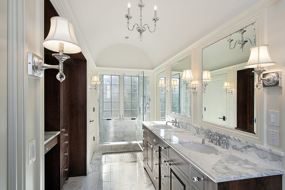 Primary bathroom with a gorgeous marble sink countertop featuring two sinks and is lighted by classy wall lights. The room has a walk-in shower area as well, with marble tiles floors and walls.