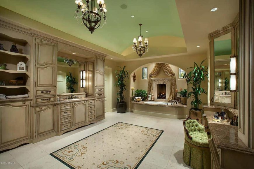 A large primary bathroom boasting a beautiful green ceiling with two gorgeous chandeliers, along with a sink counter, a powder desk area and an elegant drop-in tub featuring a fireplace on the side.