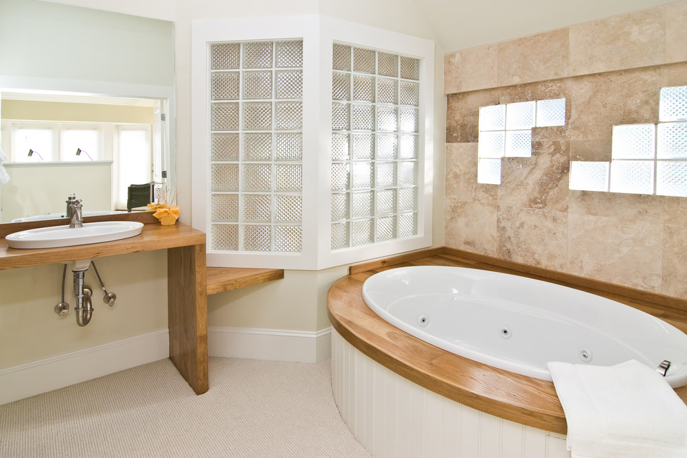 Small primary bathroom with a wooden sink counter and a charming deep soaking tub.