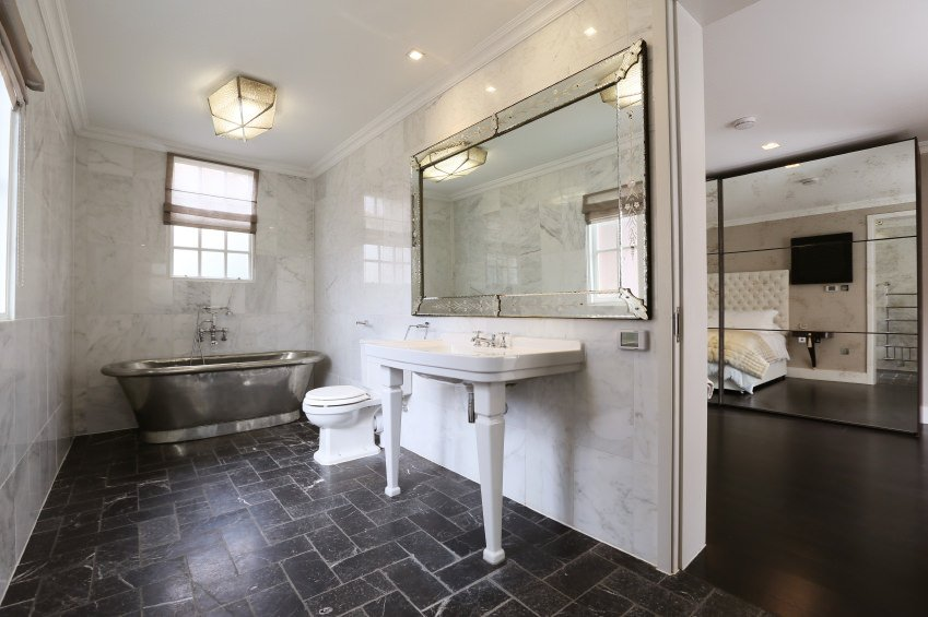 A primary suite boasting a personal bathroom with attractive black tiles flooring. It has a sink counter and a freestanding soaking tub on the side.