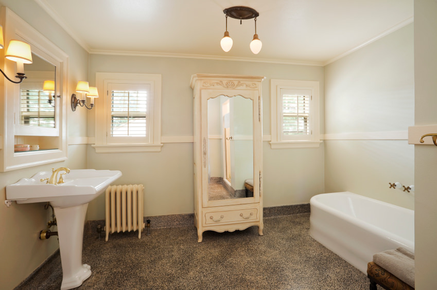 Spacious primary bathroom with custom flooring and a regular ceiling. It offers a pedestal sink lighted by classy wall lights along with a freestanding soaking tub on the side.