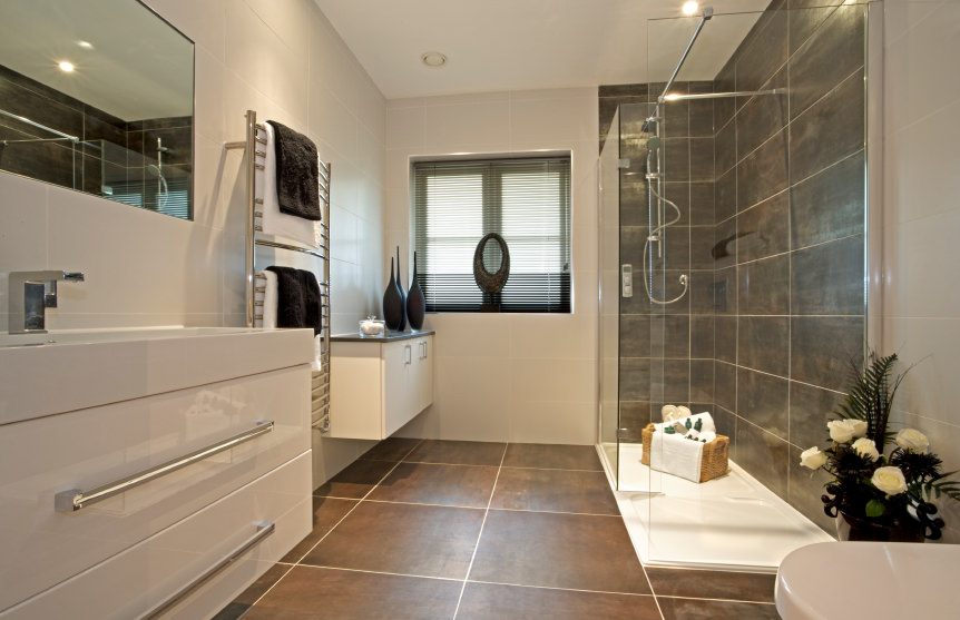 Primary bathroom featuring large tiles flooring and a modern sink counter. There's also a walk-in shower with tiles walls.