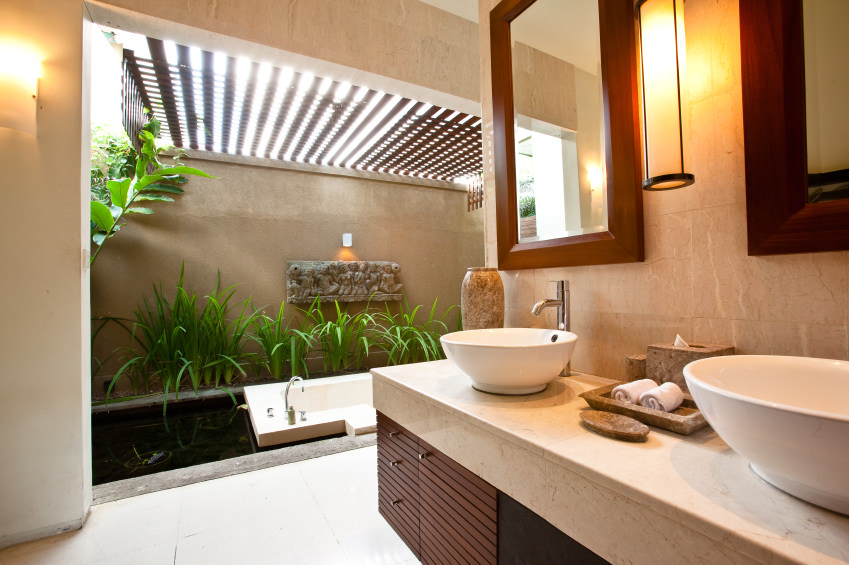 Modern primary bathroom boasting a sink counter with two vessel sinks and a deep soaking tub on the side surrounded by green plants and a custom ceiling.