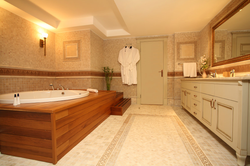 Spacious primary bathroom boasting a large deep soaking tub set on a wooden platform and is under the room's tray ceiling. The room has classy tiles flooring and walls.