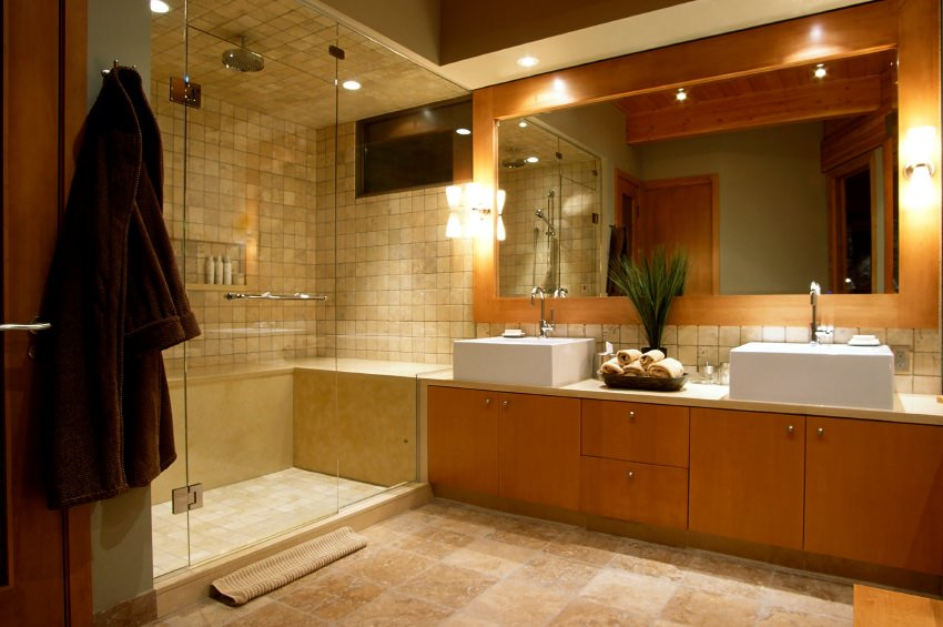 Modern primary bathroom featuring a large walk-in shower with a TV along with a sink counter featuring a pair of large vessel sinks, lighted by classy wall lights.