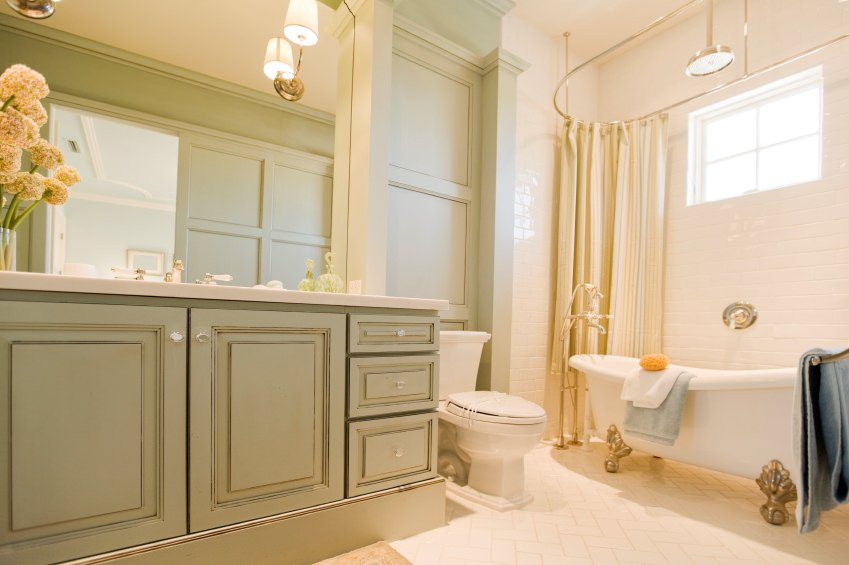 Primary bathroom featuring tiles flooring and a tall ceiling. This bathroom offers a sink counter lighted by wall lights along with a classy freestanding tub on the side.