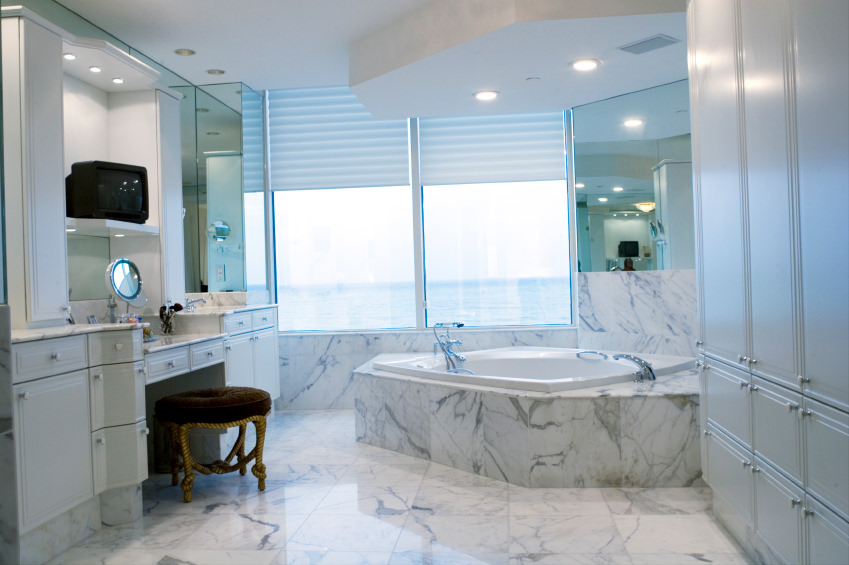 A look at this primary bathroom's powder desk area and a corner drop-in soaking tub on a marble tiles platform matching the marble tiles flooring.