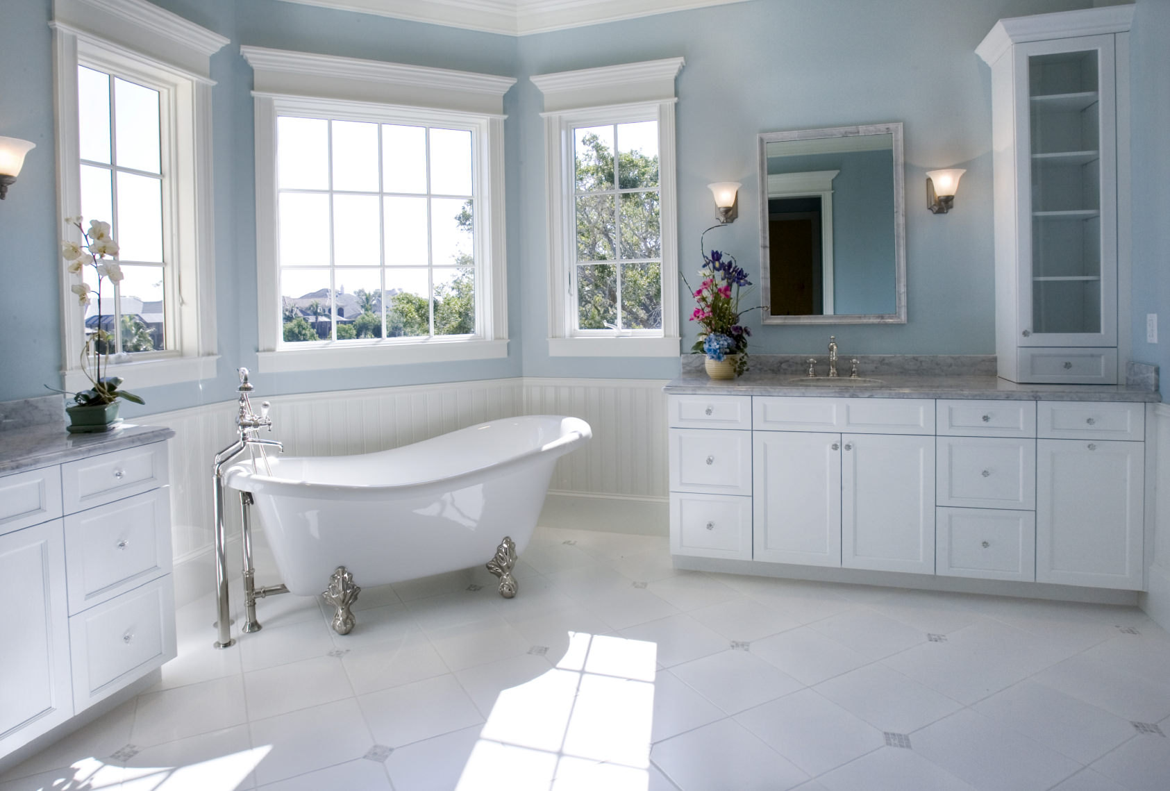 Large primary bathroom featuring white tiles flooring and blue walls. The room offers sink counters with wall sconces along with a freestanding tub by the windows.
