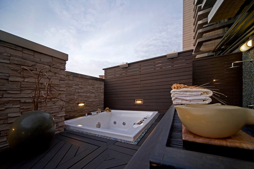 An outdoor bathroom boasting a deep soaking tub and a sink counter with vessel sinks. The flooring of the area looks stylish as well.
