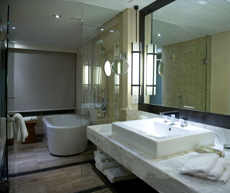 This primary bathroom features a walk-in shower and freestanding tub area. It also has a thick gorgeous marble floating vanity with a large vessel sink.