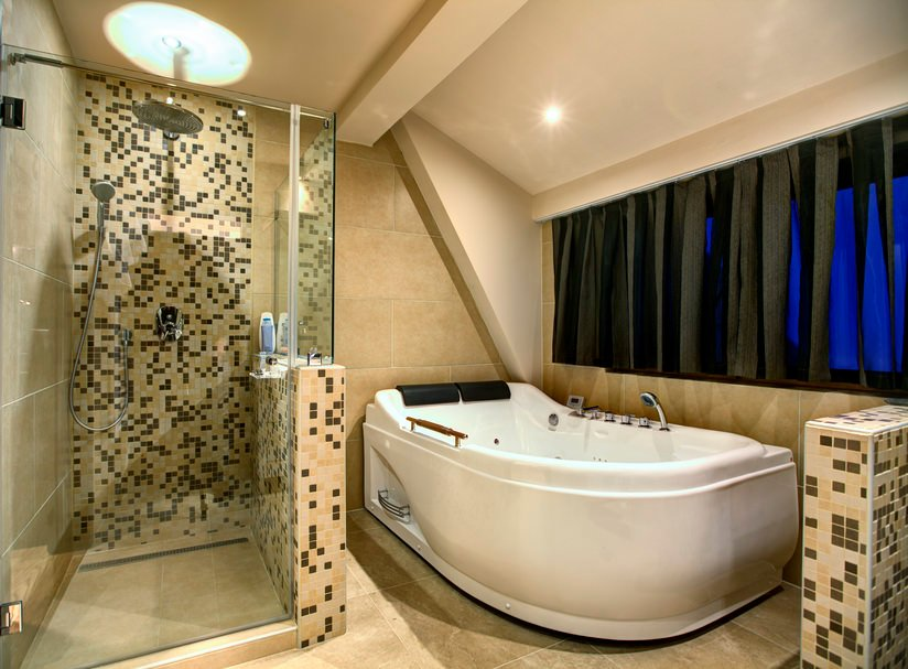 A focused look at this bathroom's large freestanding deep soaking tub and a walk-in shower room with stylish tiles walls.