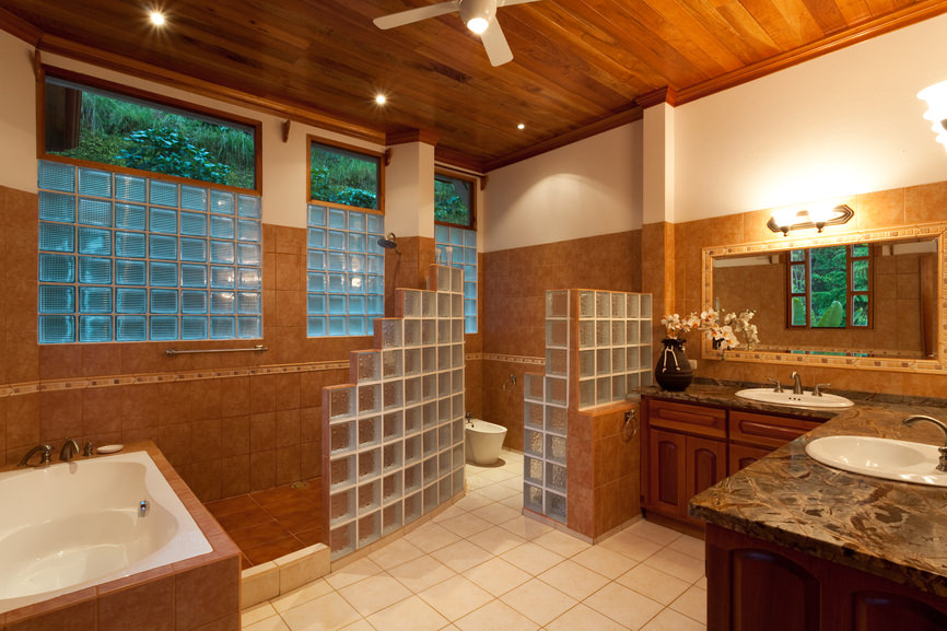 Primary bathroom with tiles flooring and a wooden ceiling, along with brown tiles walls. The room offers a custom toilet and shower area, along with a drop-in deep soaking tub and an L-shaped sink counter lighted by wall lights.