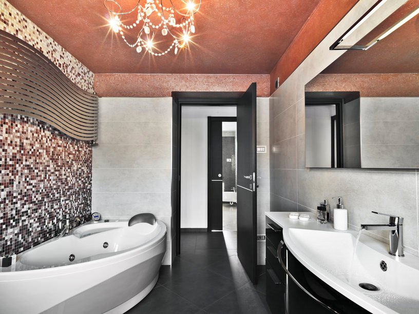 Primary bathroom featuring a stunning tiles wall and a red ceiling lighted by a glamorous chandelier. The room offers a modern freestanding tub and a stylish sink counter.