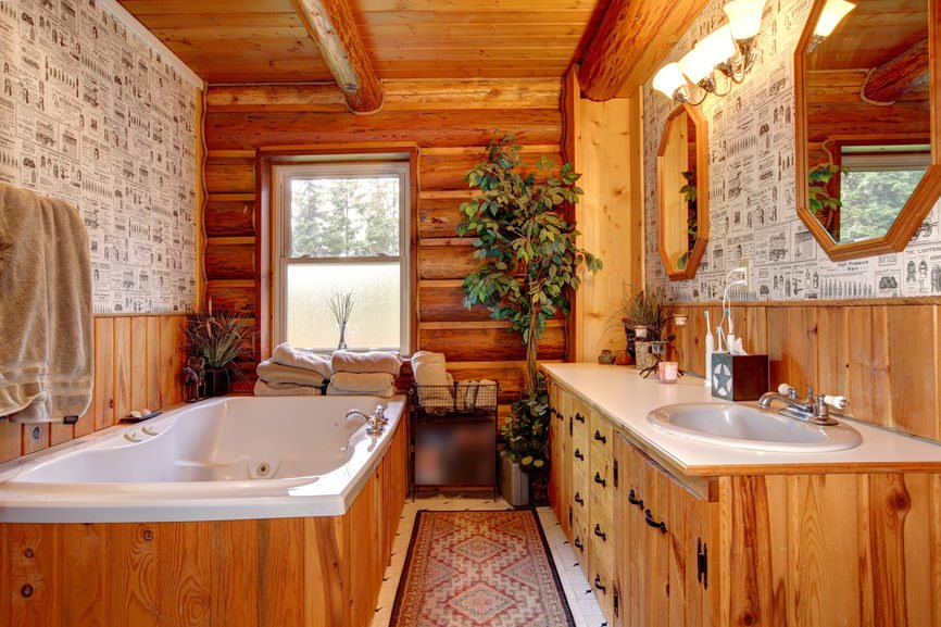 Small primary bathroom with a wooden ceiling with beams and a rustic wall, along with a large drop-in deep soaking tub and a sink counter lighted by wall lights.