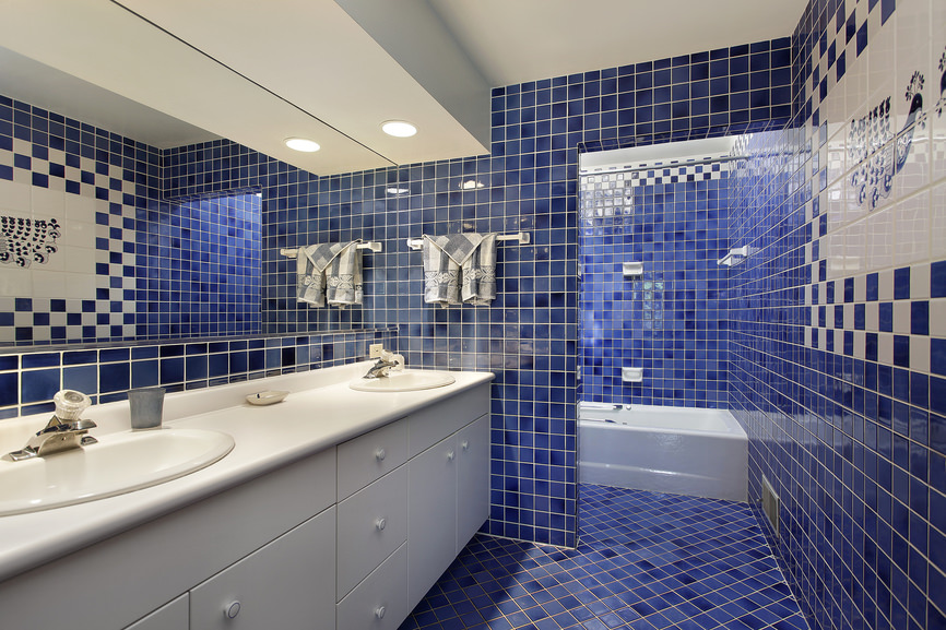 Medium-sized primary bathroom boasting blue tiles floors and walls. It offers a sink counter with two sinks, along with a bathtub and shower area.