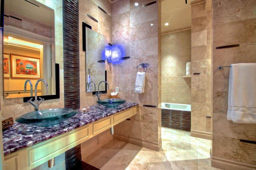 This primary bathroom boasts a floating vanity with a stunning sink countertop and has glass vessel sinks. There's a drop-in tub and a shower area.