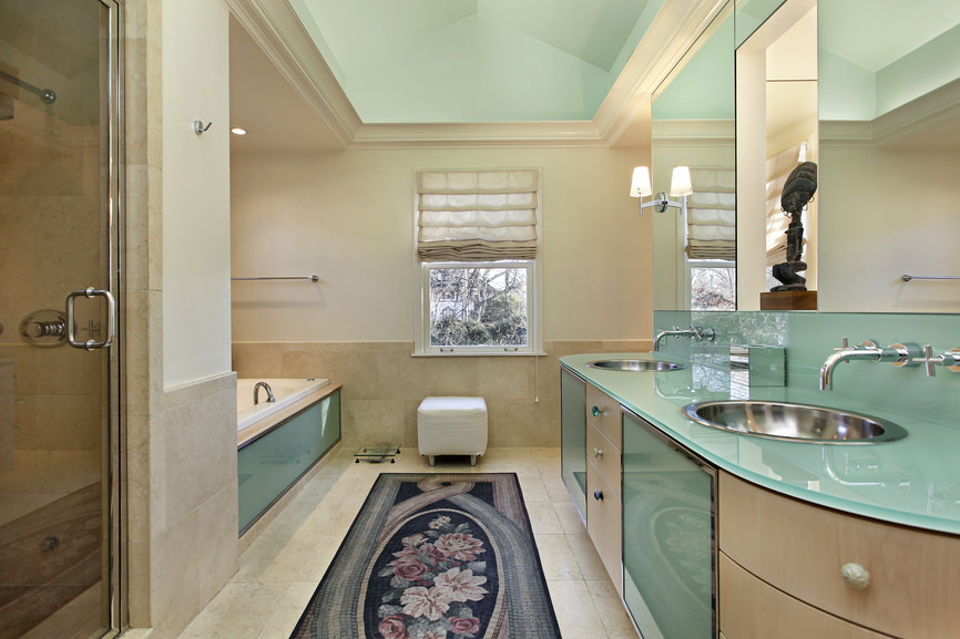 This primary bathroom boasts a gorgeous green sink counter with two sinks and a drop-in tub on the side. There's a walk-in shower room as well.