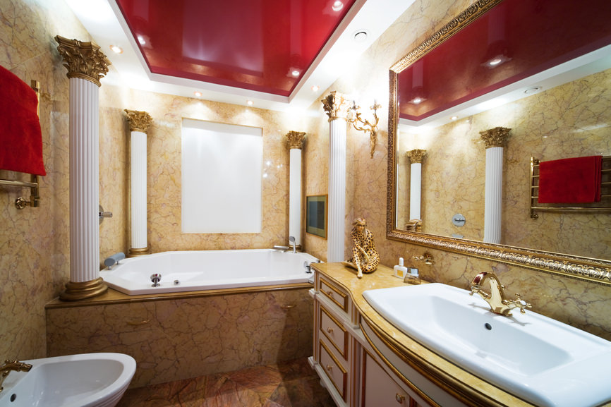 A luxurious primary bathroom boasting an elegant Romantic-style bathtub surrounded by decorated walls and a white and red tray ceiling.