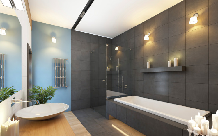 This primary bathroom boasts gray tiles walls and floors along with a white ceiling. There's a drop-in deep soaking tub with a built-in shelving nearby, lighted by wall sconces.