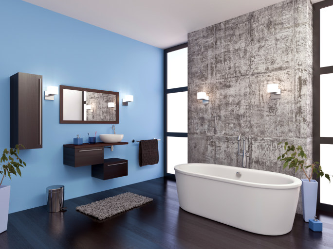 Modern primary bathroom featuring a blue and a gray wall, along with hardwood flooring. It has a small custom floating vanity with a small vessel sink, along with a freestanding deep soaking tub lighted by modern wall lights.