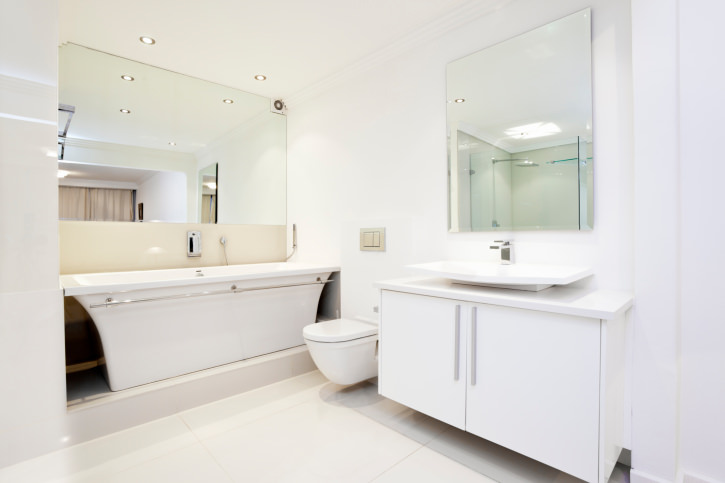 A bright primary bathroom with white tiles floors, white walls and a white ceiling. There's a white sink counter with a vessel sink, along with a freestanding deep soaking tub on the side.