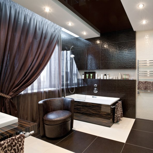 A primary bathroom boasting a custom sink counter and a custom bathtub and shower combo. The custom ceiling adds style to the room as well.