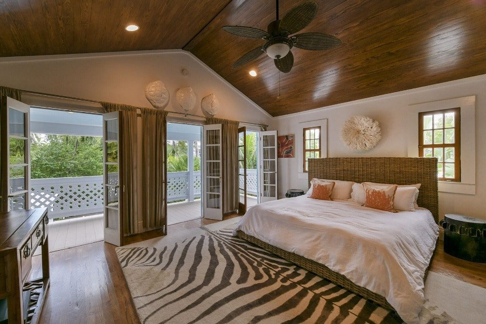 A bedroom suite featuring a tall wooden ceiling and hardwood flooring. It offers a large bed set and doorways leading to the home's balcony deck with open glass doors.