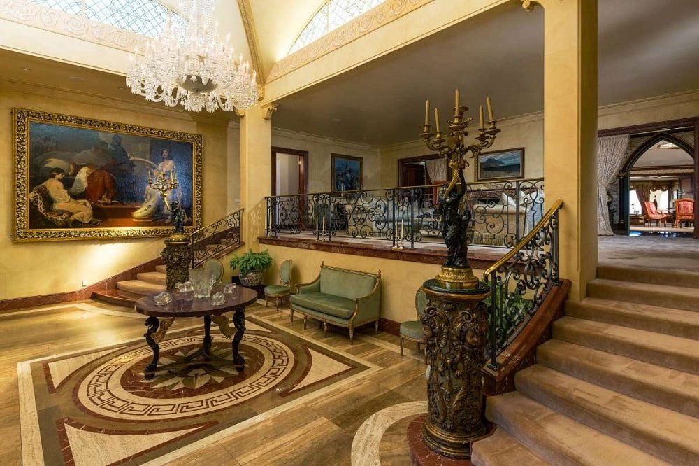 Upon entry of the house, you are welcomed by this foyer that has a large crystal chandelier hanging over a round dark wooden table on a patterned marble floor.