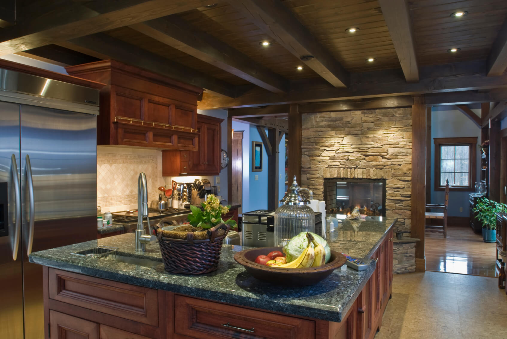 This is a dark kitchen with dark brown wooden cabinetry on its kitchen island and the wooden structure that houses the oven and fridge. These are matched by the dark wooden ceiling with exposed wooden beams and are all complemented by the textured stone fireplace.
