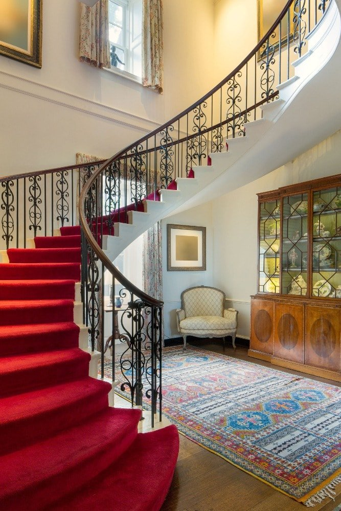 Entry hall featuring the spiral staircase with gorgeous red carpeted steps adorned with intricate wrought-iron railings. Beside the staircase is an armchair beside a display cabinet.