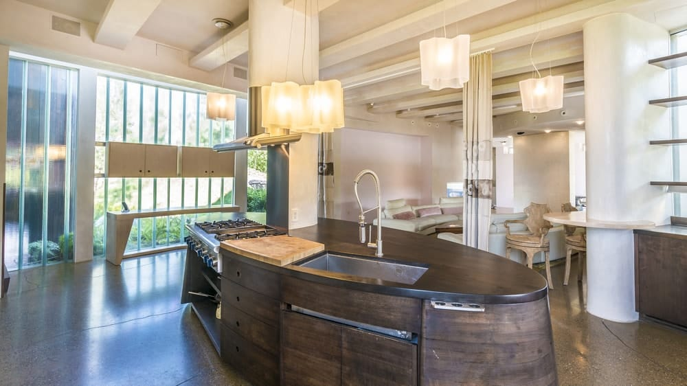 A look at this kitchen's custom island that looks absolutely eye-catching. It is lighted by charming pendant lights.
