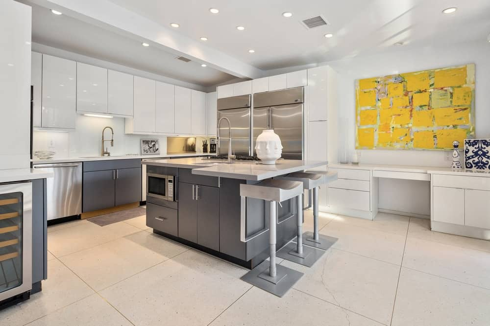 Spacious kitchen featuring large tiles flooring and a custom white ceiling with recessed ceiling lights.