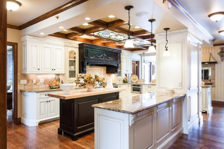 This kitchen has a dark wooden kitchen island in the middle of white built-in cabinetry and a peninsula. These are then topped with dark brown wooden beams of the ceiling that matches the hardwood flooring.
