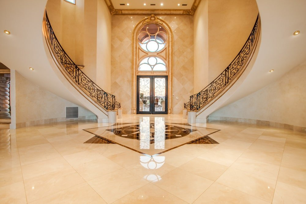 Upon entry of the mansion, you are welcomed by this beige marble foyer with a tall ceiling and a couple of curved stairs.